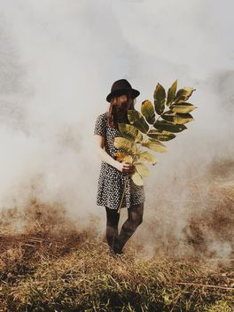 Girl holding branch with big leaves in misty forest - бесплатный image #271719