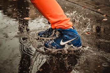 Close-up of feet in sneakers in the puddle - бесплатный image #273789