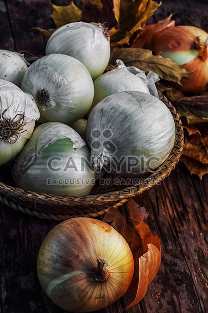 Onions in basket and on wooden background - Free image #302029