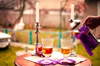 warm tea with cinnamon candles in candlesticks on the table outdoors - image gratuit #327279