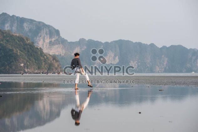 Woman walking carefully on a beach - бесплатный image #332919