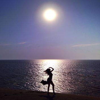 Girl on seashore at sunset - бесплатный image #338479