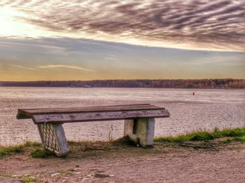 Bench on shore of lake at sunset - Free image #338559