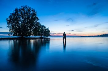 Man in sea at sunset - image #338579 gratis