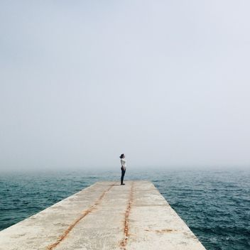 Girl on pier in sea - Free image #341339