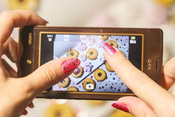 Smartphone decorated with tinsel in woman hands - image gratuit #342179