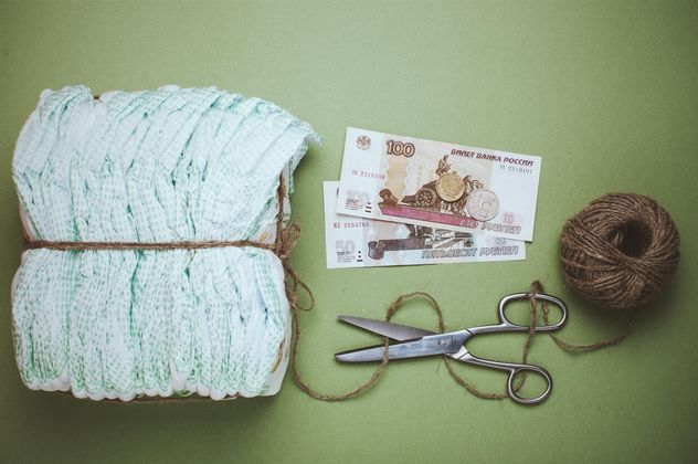 Diapers, skein of thread and scissors on green background. Diapers for 3 dollars, Cheboksary, Russia - Free image #342559