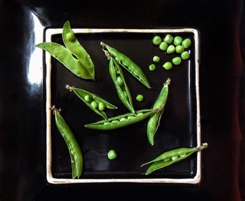 Green peas on black plate - бесплатный image #342589