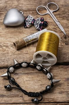 Bracelet and objects for sewing on wooden background - бесплатный image #342599