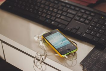 Smartphone with earphones lying on work place next to black keyboard - бесплатный image #343509