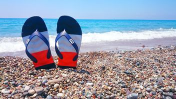 Flip flops sticking from pebble - image #344019 gratis
