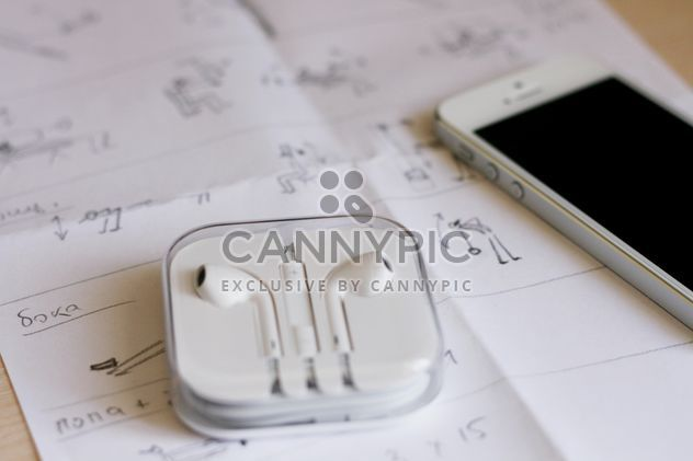 Closeup of smartphone and earphones on paper - бесплатный image #345049
