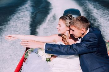 Happy wedding couple in boat on lake - бесплатный image #345109