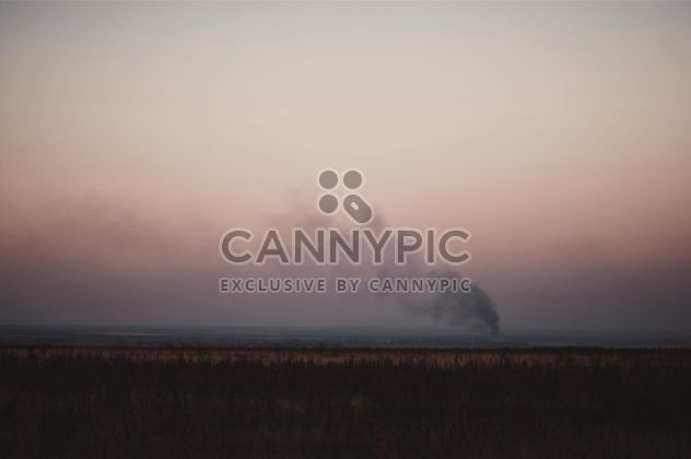 Landscape with smoke in field at sunset - image #346299 gratis