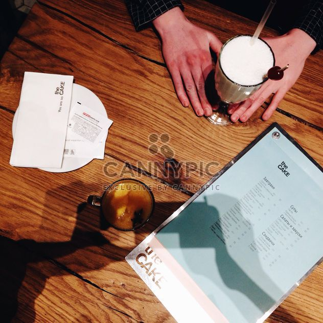 Hands and glass of milk shake on wooden table - Free image #346569