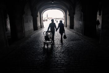 Happy family with baby walking in street, black and white - Free image #346579