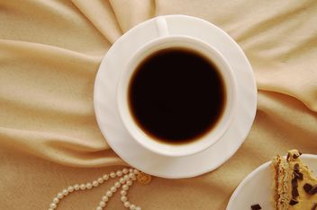 Cup of black coffee on beige cloth - бесплатный image #346929