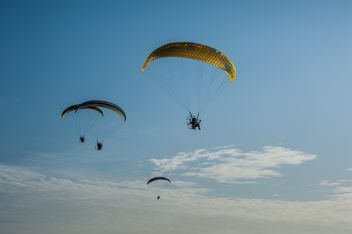 Paragliders flying in blue sky - бесплатный image #347309