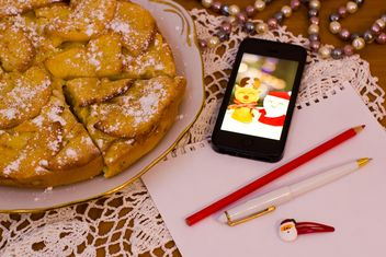 Apple pie, smartphone and paper on table - бесплатный image #347929