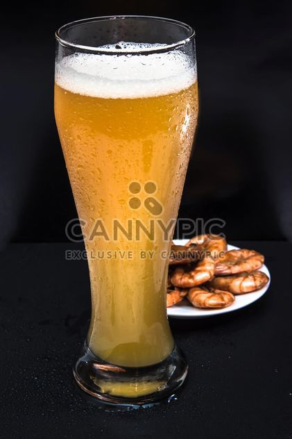 unfiltered cold foamy beer in a tall glass with a snack of fried shrimp - image gratuit #381019