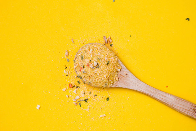 Top view of wooden spoon with yellow spice on yellow background - Free image #448899