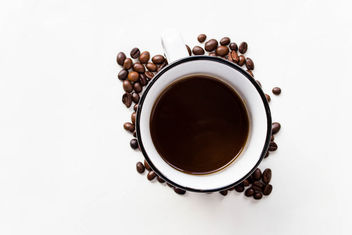 A cup of black coffee and coffee beans - image #449069 gratis