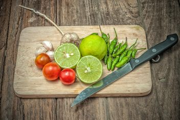 Lime, vegetables and knife on wooden cutting board - Free image #452419