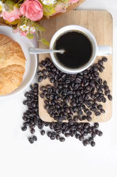 Cup of coffee with croissant, flowers and coffee beans - бесплатный image #452569