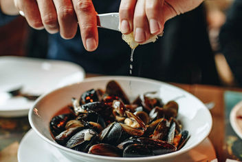 Hands squeezing lemon over plate with mussels. - бесплатный image #452879