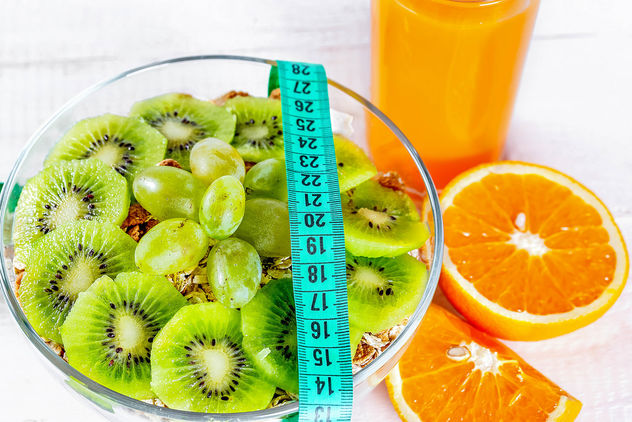 Proper diet for health and a beautiful figure-porridge and orange juice with measuring tape - бесплатный image #456789
