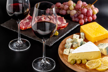Glasses of red wine on a dark background with various delicious snacks - Free image #475899